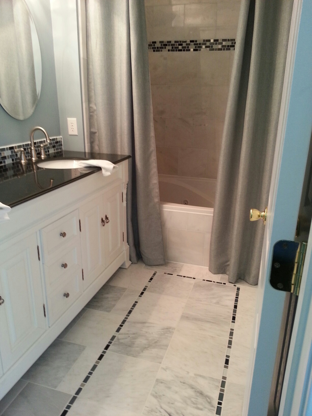 pictured here is a fabulous bathroom remodel with marble floor and shower wall tiles accented with a beautiful colored glass mosaic tile